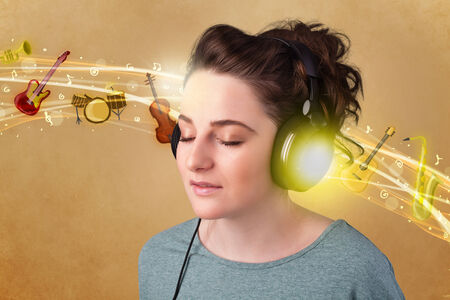 Pretty young woman with headphones listening to music, instruments concept Stock Photo