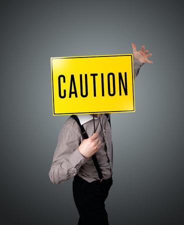 se�alizacion de seguridad: Empresario de pie y la celebraci�n de una se�al de precauci�n amarillo en frente de su cabeza