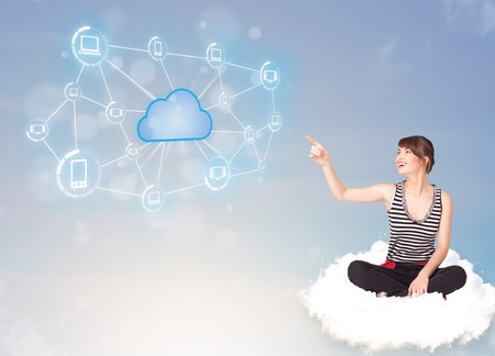 Happy young woman sitting on cloud with cloud computing photo
