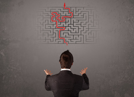 Business man looking at a maze and the way out on brown wall photo
