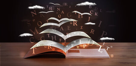 Pages and glowing letters flying out of a book on wooden deck Stock Photo