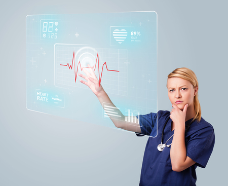 Young nurse standing and pressing modern medical type of buttons photo