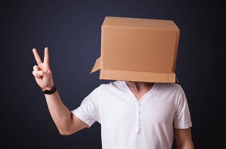 masquerader: Young man standing and gesturing with a cardboard box on his head