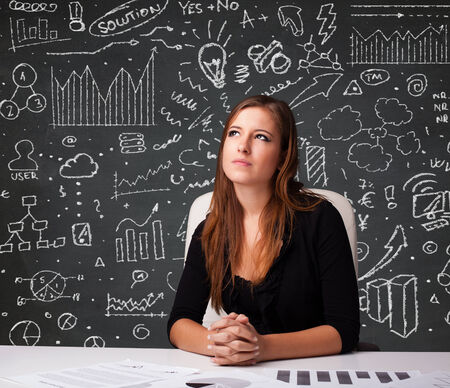 economic growth: Pretty young businesswoman sitting at desk with business scheme and icons