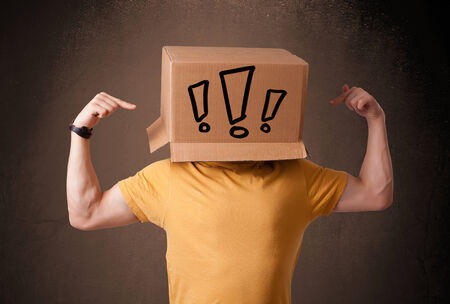masquerader: Young man standing and gesturing with a cardboard box on his head with exclamation point Stock Photo