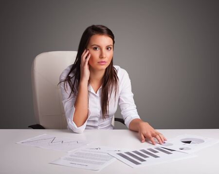 Beautiful young businesswoman sitting at desk and doing paperwork photo