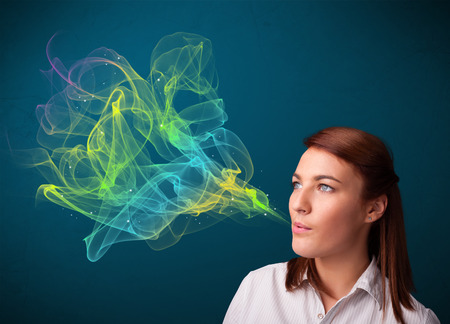 Pretty young lady smoking cigarette with colorful smoke photo