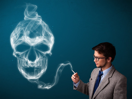 Handsome young man smoking dangerous cigarette with toxic skull smoke Stock Photo