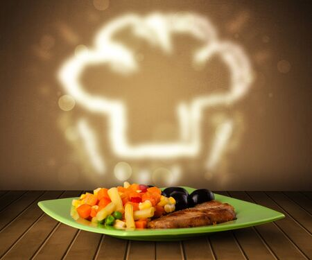 Delicious food plate with chef cook hat on wood deck photo