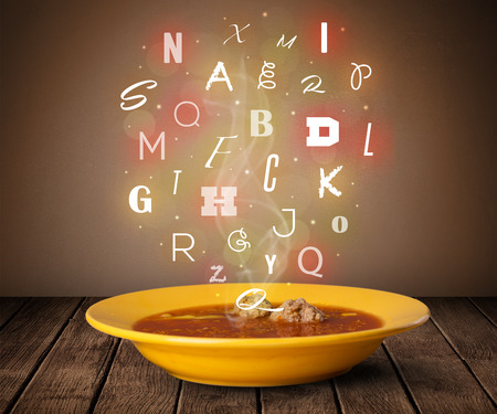 Colorful letters coming out of home cook soup bowl on wood deck photo