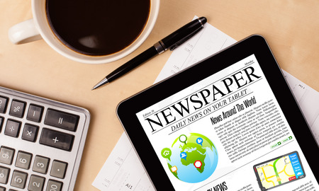 stock news: Workplace with tablet pc showing news and a cup of coffee on a wooden work table close-up Stock Photo