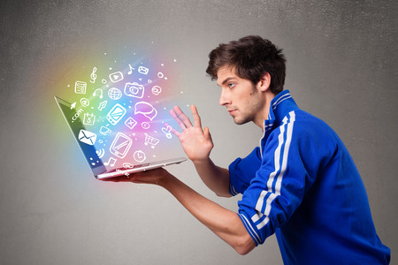 Casual young man holding laptop with colorful hand drawn multimedia symbols photo
