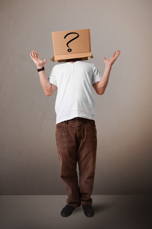 masquerader: Young man standing and gesturing with a cardboard box on his head with question mark Stock Photo