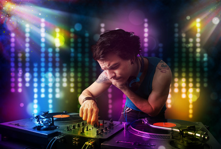 Young Dj playing songs in a disco with light show photo
