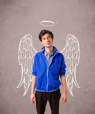 Young man with angel illustrated wings on grungy background Stock Photo