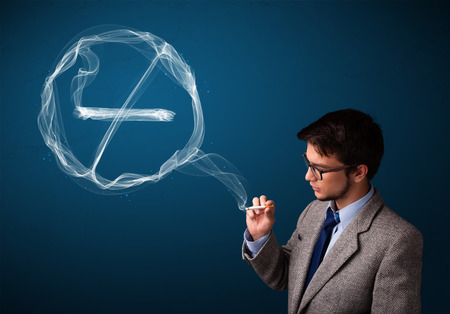 inhale: Handsome young man smoking unhealthy cigarette with no smoking sign Stock Photo