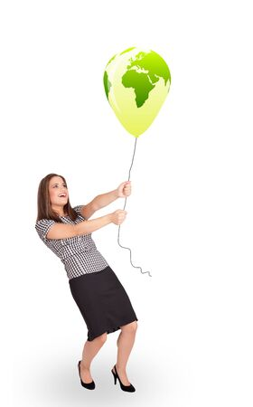 Happy young lady holding a green globe balloon photo