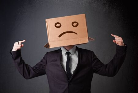 woeful: Businessman standing and gesturing with a cardboard box on his head with sad face