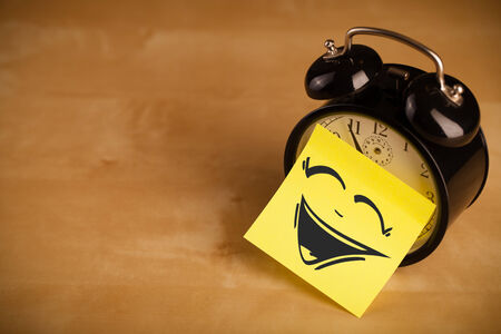 clock face: Drawn smiley face on a sticky note sticked on alarm clock Stock Photo