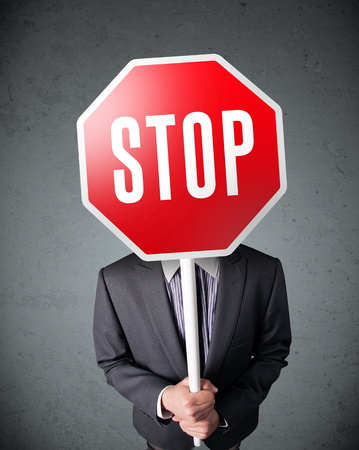 Businessman standing and holding a stop sign in front of his head photo