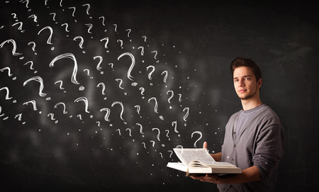 confused man: Confused man reading a book with question marks coming out from it