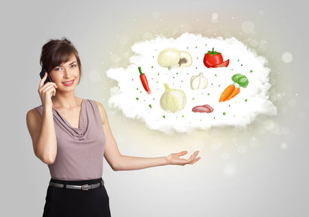 nutritional: Pretty woman presenting a cloud of healthy nutritional vegetables concept Stock Photo