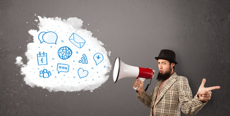 urgent announcement: Young man shouting into loudspeaker and modern blue icons and symbols come out Stock Photo