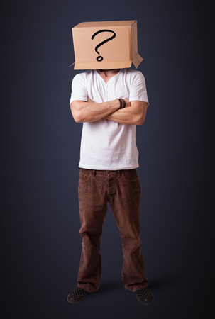 the human face: Young man standing and gesturing with a cardboard box on his head with smiley face