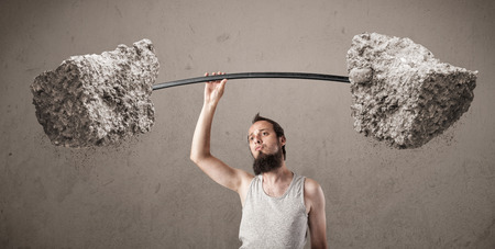 Funny skinny guy lifting large rock stone weights photo