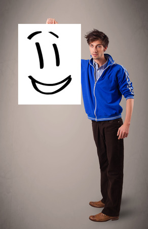 Handsome young boy holding smiley face drawing photo
