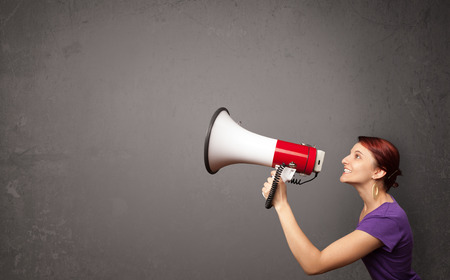 Pretty girl shouting into megaphone on copy space background photo