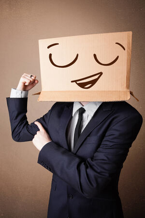 boxy: Businessman standing and gesturing with a cardboard box on his head with smiley face Stock Photo
