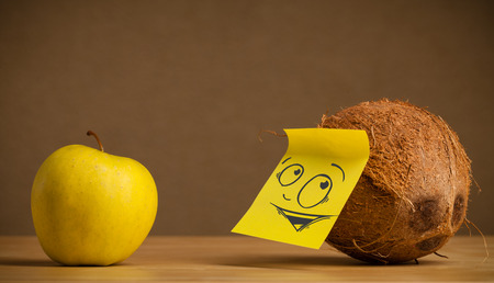 reacting: Coconut with sticky note reacting at apple Stock Photo