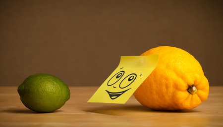 reacting: Lemon with sticky note reacting to lime Stock Photo