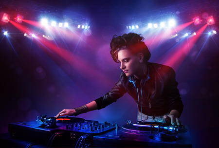 Teenager Dj girl mixing records in front of a crowd on stage photo
