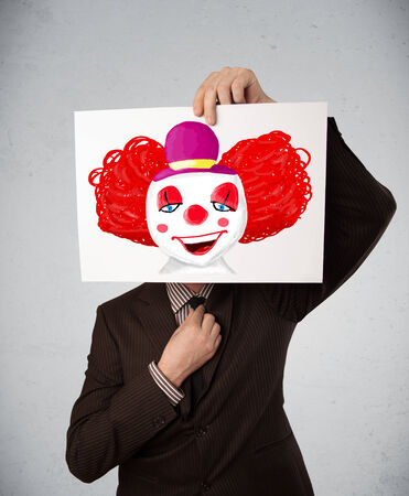 Young businessman holding a cardboard with a clown on it in front of his head photo