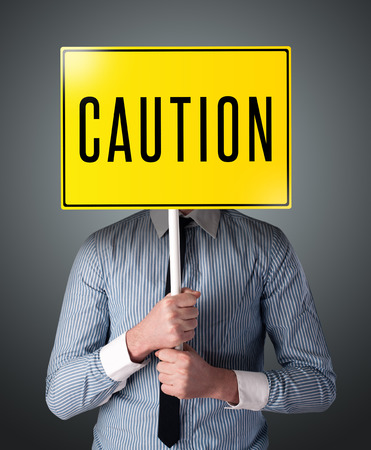 Businessman standing and holding a yellow caution sign in front of his head