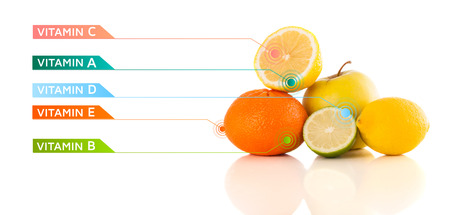 Healthy fruits with colorful vitamin symbols on white background photo