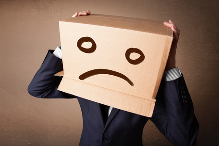hiding face: Businessman standing and gesturing with a cardboard box on his head with sad face