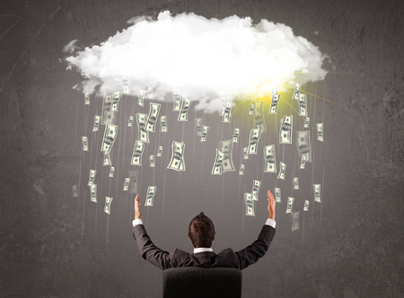 Business man in suit looking at cloud with falling money and sun photo