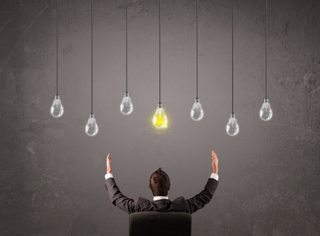 Businness guy in front of bright idea light bulbs concept Stock Photo