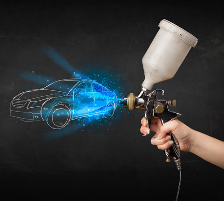 Worker with airbrush gun painting hand drawn white car lines photo