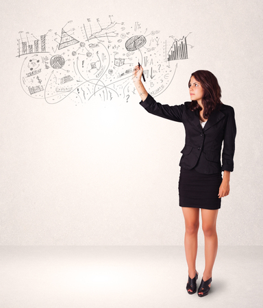 Pretty girl sketching graphs and diagrams on white wall photo