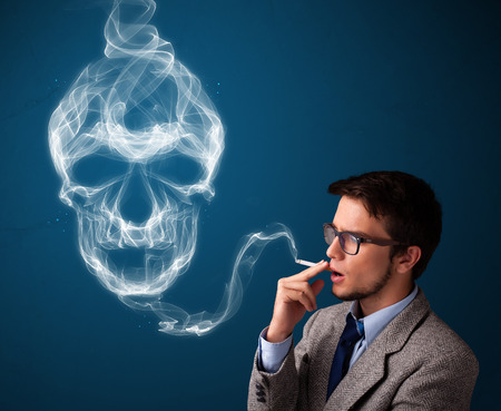 cigare: Handsome young man smoking dangerous cigarette with toxic skull smoke Stock Photo