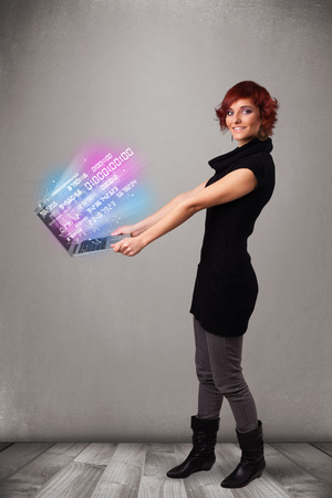 Attractive casual woman holding laptop with exploding data and numers photo