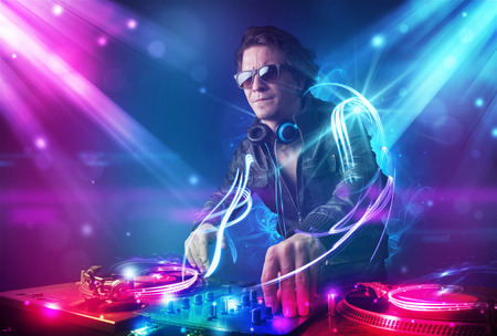 dance party: Young energetic Dj mixing music with powerful light effects