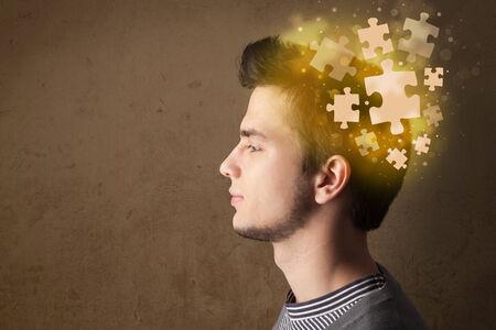 persona pensando: Persona joven que piensa con la mente rompecabezas que brilla intensamente en fondo sucio Foto de archivo