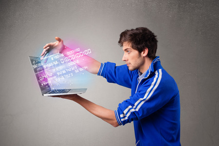 Casual young man holding laptop with exploding data and numbers photo