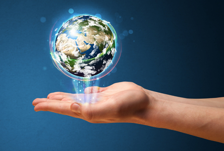 businessman carrying a globe: Young businessman holding in his hand a glowing earth globe