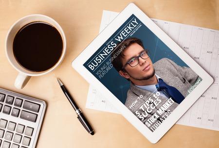 Lugar de trabajo con tablet pc que muestra portada de una revista y una taza de café en una mesa de trabajo de madera de cerca Foto de archivo